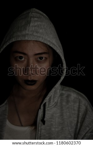 Face of Asian woman with black mouth wearing hood on dark background, Dark tone style, Scary woman concept, Halloween day #1180602370