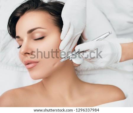 face of beautiful woman while procedure jet peeling, facial treatment