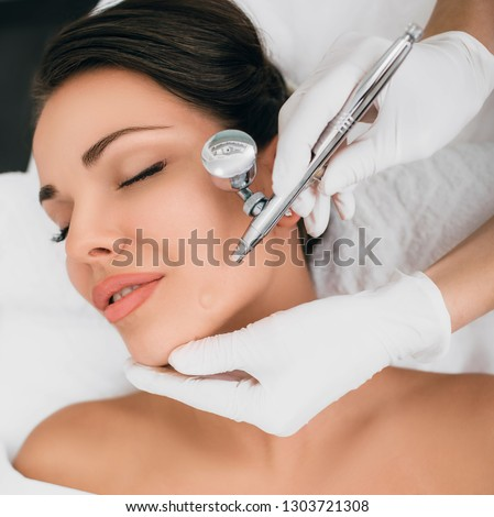 face of beautiful woman while procedure jet peeling, facial treatment #1303721308