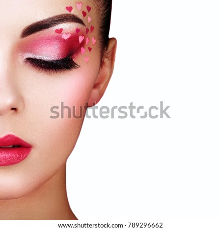 Face of beautiful woman with holiday makeup heart. Valentine's day make-up. Lips in pink lipstick. Makeup detail. Face of girl on a white background