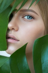 Face of beautiful young woman with clean perfect skin covered by leaves. Portrait of beauty model with natural nude make up and long eyelashes. Spa, skincare and wellness. Close up.