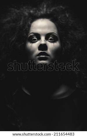 face of crazy woman with fluffy hair in dark monochrome image