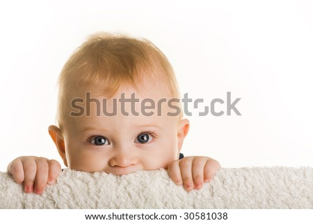 Face of curious baby peeping out of board over white background