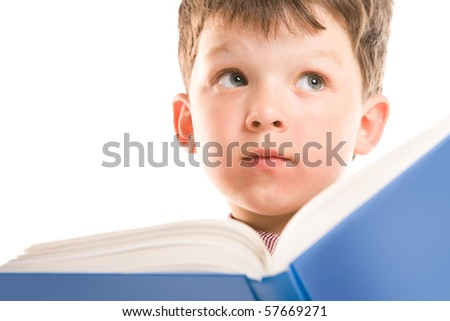 Face of cute schoolboy thinking and looking aside while reading textbook