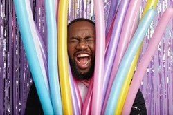 Face of dark skinned man through party modeling balloons, screams loudly, shows white perfect teeth, prepares for celebration special occasion. Unshaven young guy exclaims, has wide opened mouth