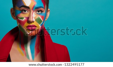 Face of fashion model, looking at camera. Beautiful woman wearing in red jacket. Fashionable girl has creative and colorful pop art make up on face, pink lipstick on plump lips.