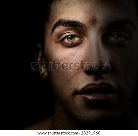 Face of handsome man with green eyes in the shadow