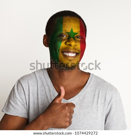 Face of happy african-american man painted with flag of Senegal. Football or soccer team fan showing thumb up, sport event, faceart and patriotism concept. Studio shot at white background, copy space #1074429272