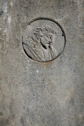 Face of Jesus Christ on cement tomb stone with copy space