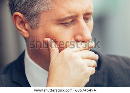 Face of pensive mature businessman covering mouth