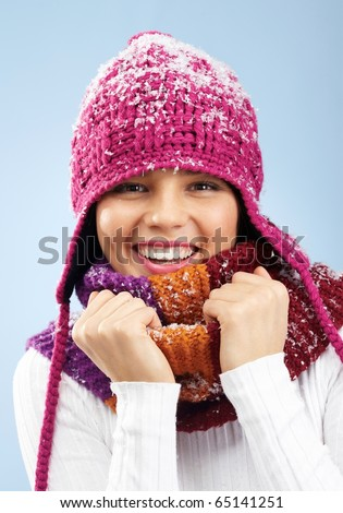 Face of pretty woman in knitted winter cap and scarf looking at camera with smile