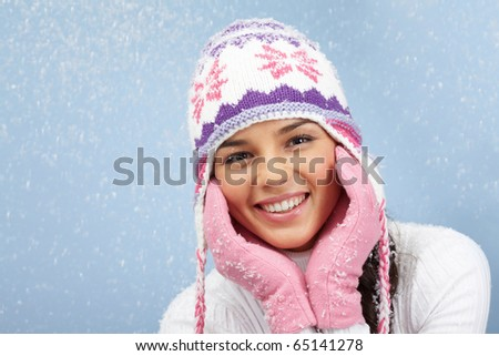 Face of pretty woman in pink gloves and knitted winter cap looking at camera with smile