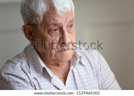 Face of senior caucasian hoary man looking away deep in sad thoughts feels lonely close up portrait, recollect memories and life moments, depressed grandfather alone indoors, yearning for wife concept