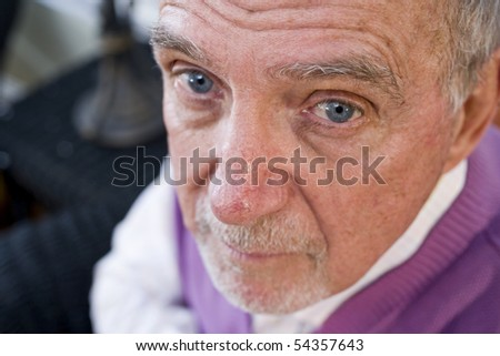 Face of serious elderly man in 70s staring at camera