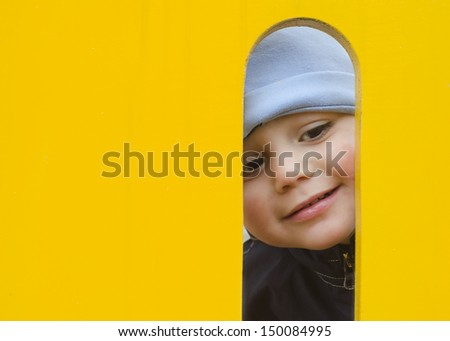 Face of small child, boy or girl, looking through a hole in a play equipment in an outdoors playground.
