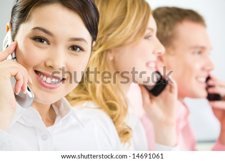 Face of smiling businesswoman making phone call and looking at camera with smile on background of two phoning people