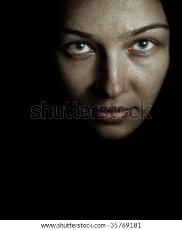Face of spooky mystery woman in the dark