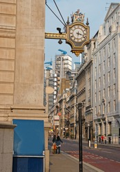 Face of the clock in the city center of London in the UK. People on the background