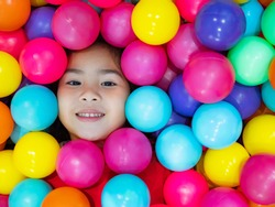 Face of the kid with smiling in the plassic ball pool
