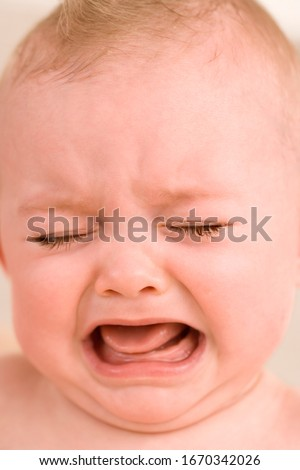 Face of unhappy baby girl crying with tears