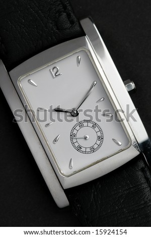 Face of wristwatch close-up over black background