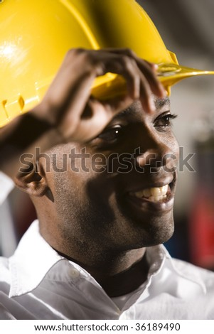 Face of young African American man in hard hat smiling