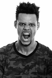 Face of young angry African man shouting