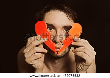 Face of young handsome man with broken paper heart closeup