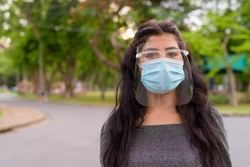 Face of young Indian woman wearing mask and face shield at the park outdoors