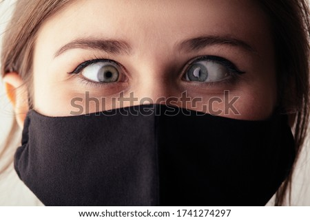 face of young woman in black mask with one eye on one point, life under quarantine and epidemic, crazy madness concept, mood fooling around, humor