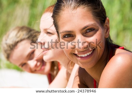 Face of young woman looking at camera on hot summer day with her friends at background