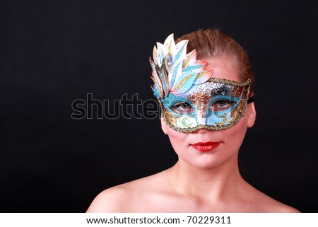 Face of young woman with carnival mask isolate on black - stock photo