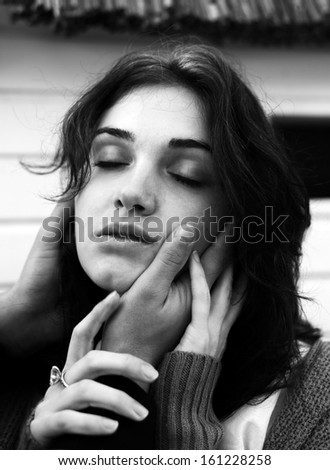 face of young woman with man's hand
