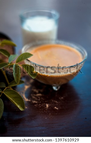 Face pack for anti-dryness on wooden surface i.e. Hing powder well mixed with honey and milk in a bowl and entire raw ingredients present on the surface. Photo stock ©