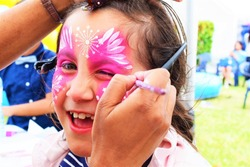 Face painting, artist painting a child as Butterfly.