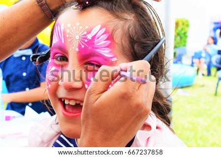 Face painting, artist painting a child as Butterfly. #667237858