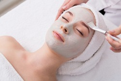 Face peeling mask, spa beauty treatment, skincare. Woman getting facial care by beautician at spa salon, side view, close-up