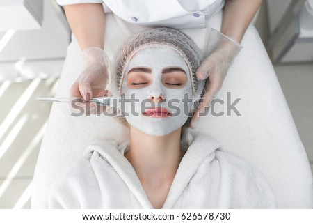 Face peeling mask, spa beauty treatment, skincare. Woman getting facial care by beautician at spa salon #626578730