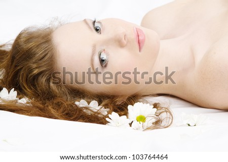 Face portrait of a beautiful model with flowers, studio photo