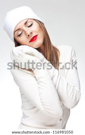 Face portrait of a young woman in white knit wool  hat and mittens