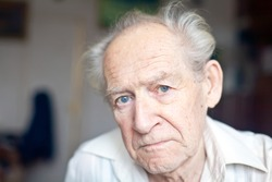 face portrait of an old unhappy frowning senior man