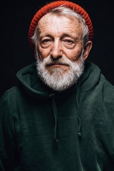 Face portrait of gloomy experienced grey-haired old-aged man with skin lined with wrinkles, dressed in warm shabby clothing as a tramp, looking seriously at camera with hopeless humble expression.