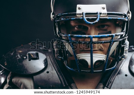 Face portrait of manly loooking young sportsman in black protective headgear and armour, looking courageously at camera, determined to win #1245949174