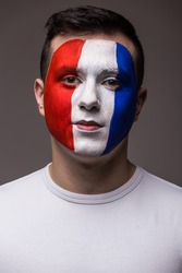 Face portrait of Pray France football fan in game  of France national  team look at camera. European football fans concept.