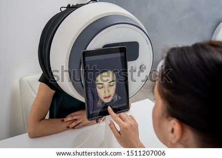 Face skin analyze system. Cosmetologist analyzing woman face. Modern technologies. Cosmetology concept