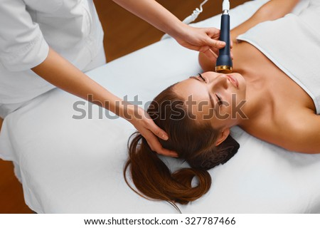 Face skin care. Beautiful young healthy caucasian woman lies on a table in a medical cosmetology spa salon getting facial skin care treatment. Ultrasound cavitation anti-aging, lifting procedure