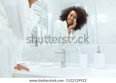 Face skin care. Girl removing makeup with cosmetic cotton pad at bathroom. Closeup portrait of beautiful smiling african woman with afro hair cleaning facial skin with white pad
