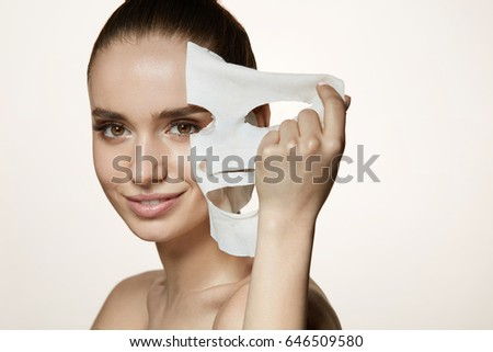 Face Skin Care. Portrait Of Beautiful Smiling Girl Removing White Sheet Mask From Healthy Fresh Skin. Closeup Of Attractive Sexy Woman With Natural Makeup And Mask On Facial Skin. High Resolution #646509580
