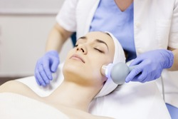 Face skin care. Woman getting facial laser treatment