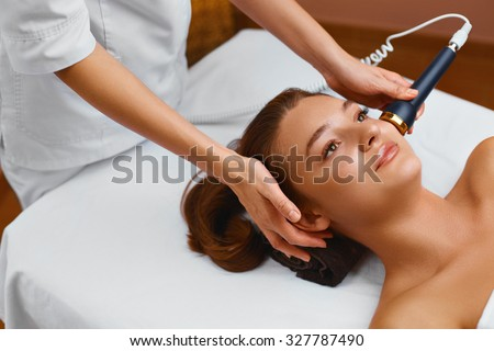 Face skin care.  Woman lies on a table in a medical beauty cosmetology spa salon getting facial skin care treatment. Ultrasound cavitation anti-aging, rejuvenation, lifting procedure. Beauty concept